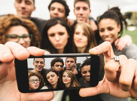 Image with group of millennials taking a selfie