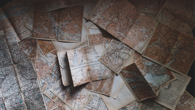 Image of a bunch of old paper maps on a table