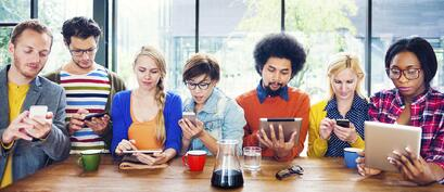 Image of a group of millennials using electronic devices
