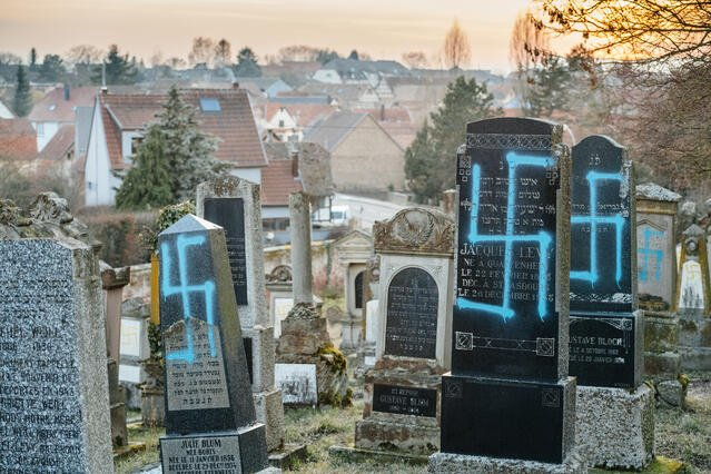 Image of headstones vandalised by spray paint